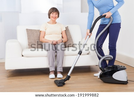 Caretaker cleaning floor with vacuum cleaner while senior woman sitting on sofa at nursing home - stock photo