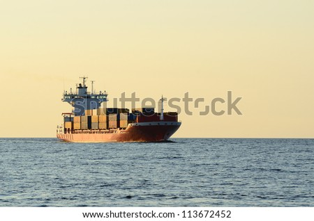 cargo container ship sailing at the sunset - stock photo