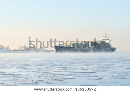 cargo container ship sailing in still frozen winter sea
