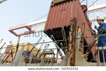 Cargo container worker - watching the loading plan . - stock photo