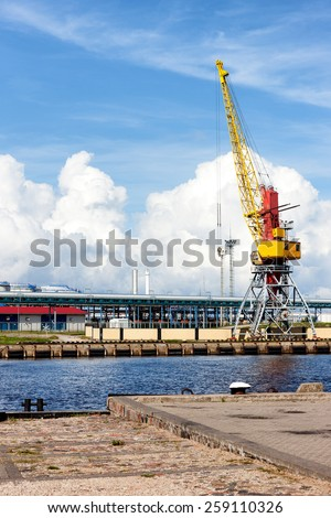 Cargo crane in the port of the Baltic against the blue sky in summer. Ventspils