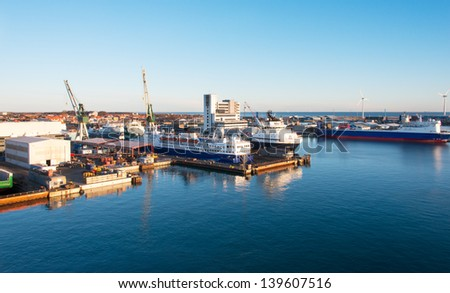 Cargo freight ship with crane at shipyard - stock photo