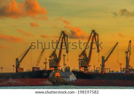 Cargo freight ship with working crane bridge in shipyard at dusk.