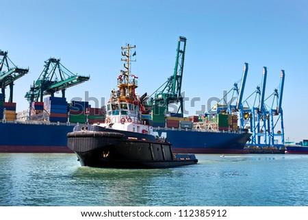 Cargo sea port. Sea cargo cranes. Tug. - stock photo