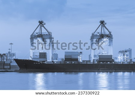 Cargo ship and crane at port reflect on river, blue color tone. - stock photo