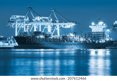 Cargo ship and crane at port reflect on river, twilight time (blue color tone). - stock photo