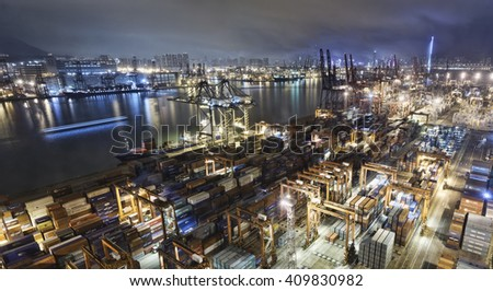 Cargo ship and crane at port reflect on sea bay, hong kong twilight time - stock photo