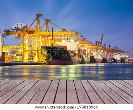 Cargo ship and crane at port with wood bridge, twilight time. - stock photo