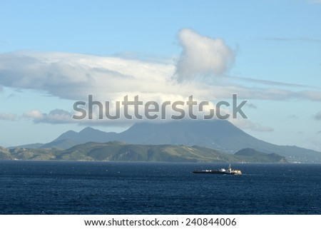 Cargo ship approaching the islands of St Kitts and Nevis in the Caribbean - stock photo