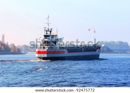 cargo ship arriving in port in autumn - stock photo