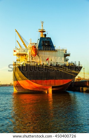 Cargo ship at sunset coming to port. - stock photo