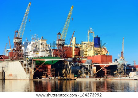 cargo ship during fixing and painting at the shipyard docks - stock photo