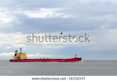 Cargo ship in open sea under cloudy blue sky - stock photo