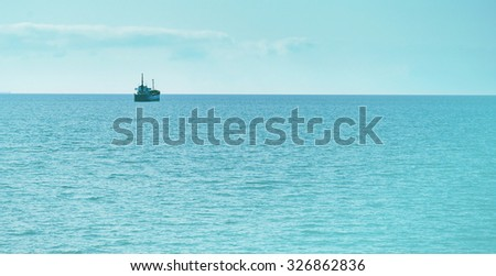 Cargo ship in the blue sea at sunny day - stock photo