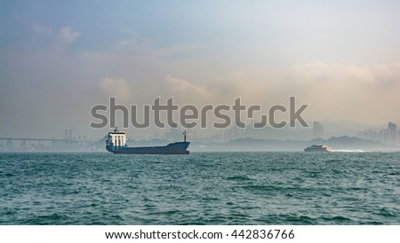 Cargo ship in the sea in Hong Kong with cityscape background and sunrise sky.