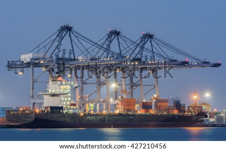 Cargo ship loading containers. - stock photo
