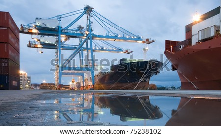 Cargo ship loading containers by night
