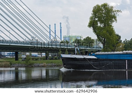 Cargo ship on the main river in front of an industrial area in Frankfurt, Germany
