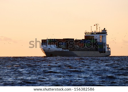 Cargo ship sailing against colorful sunset - stock photo