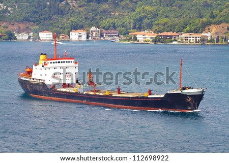 Cargo ship sailing along the shore - stock photo