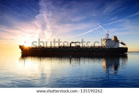 Cargo ship sailing away against colorful sunset - stock photo