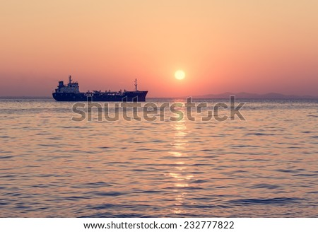 Cargo ship sailing in late afternoon with setting sun - stock photo
