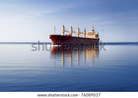 cargo ship sailing in still water near port of Riga - stock photo
