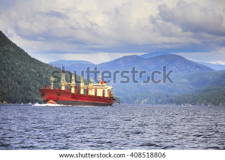 Cargo ship sailing in the fjord from Port Alberny. Vancouver island. Canada. - stock photo