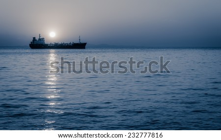 Cargo ship sailing with full moon rising above it - stock photo