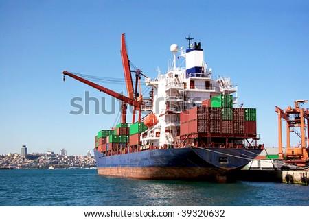Cargo ship under loading in port - stock photo