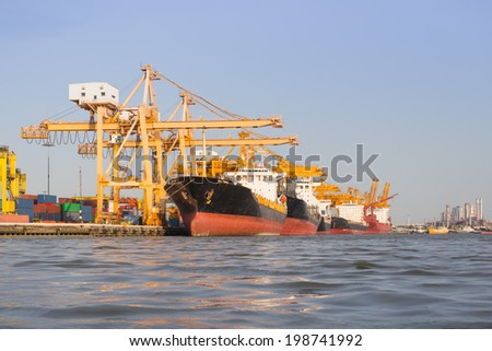 Cargo ship unloading container at port, day time. - stock photo