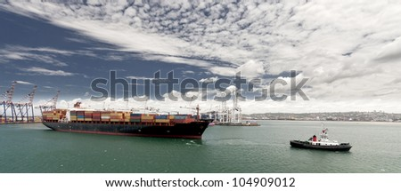 Cargo ship with tug boat assistance leaving the port of Durban South Africa - stock photo