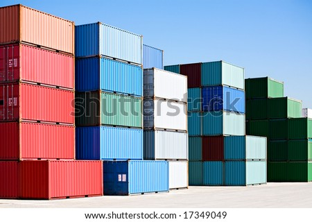 cargo shipping containers stacked at harbor freight terminal under clear blue sky - stock photo