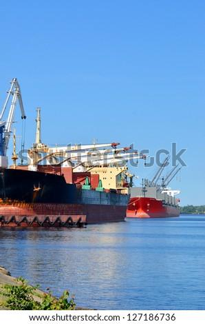 cargo ships loading in cargo terminal - stock photo