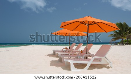 Caribbean Beach with Lounge Chairs and Umbrellas - stock photo