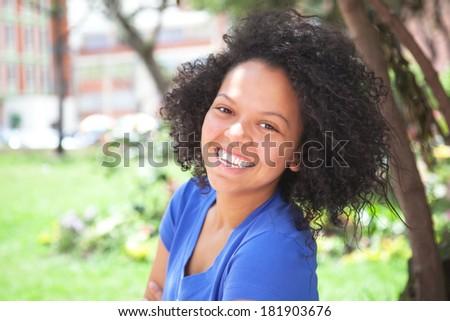 Caribbean girl in blue shirt laughing at camera - stock photo