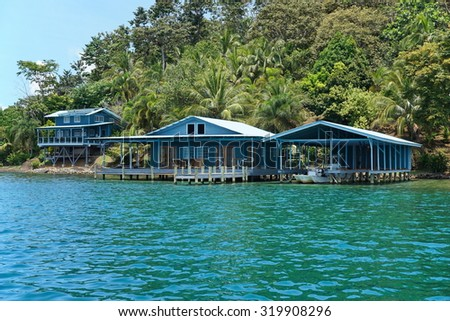 Caribbean home and boat house over the water with lush tropical vegetation on the coast, Panama, Central America - stock photo