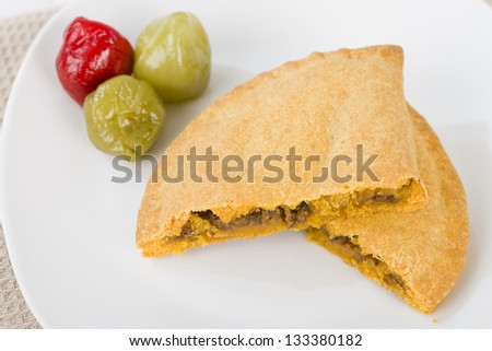 Caribbean Lamb Pattie - Jamaican spicy minced lamb with onions and peppers in short crust pastry and scotch bonnet chillies on a white background. - stock photo