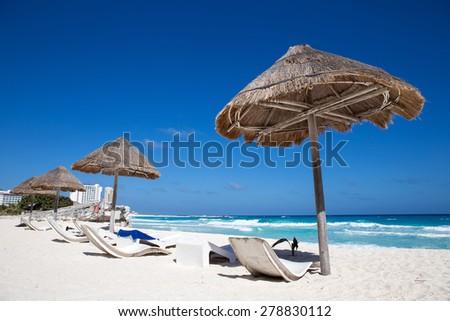Caribbean sea coastline with grass sun umbrellas and wooden beach beds. Vacation concept  - stock photo