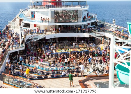 Caribbean Sea, July 10, 2011: Passengers aboard the Carnival Freedom gather on the Lido Deck at the start of a Caribbean cruise. - stock photo