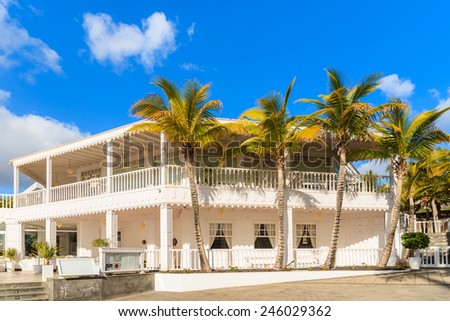 Caribbean style building and palm trees in Puerto Calero marina, Lanzarote, Canary Islands, Spain - stock photo