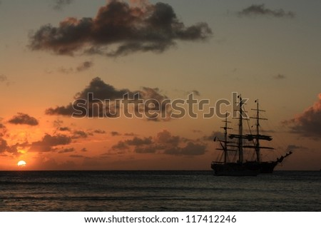 Caribbean sunset and silhouett of the ship - stock photo