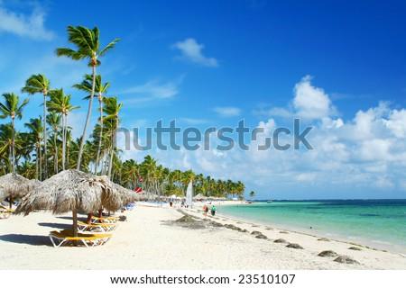 Caribbean tourist resort beach fringed grass umbrellas and beach chairs. - stock photo