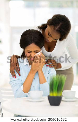 caring african woman comforting crying mother
