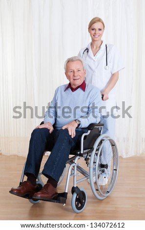 Caring Doctor Helping Handicapped Senior Patient Indoors - stock photo
