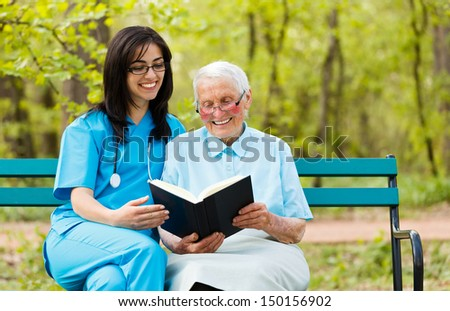 Caring doctor with kind elderly lady sitting on a bench reading a book. - stock photo