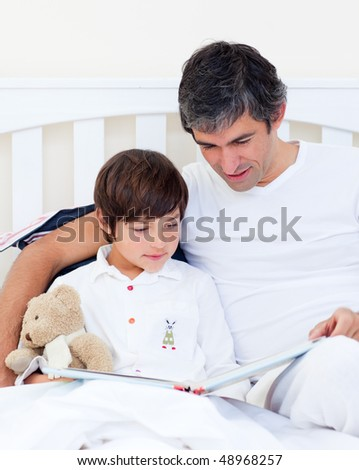 Caring father reading with his son sitting on a bed - stock photo