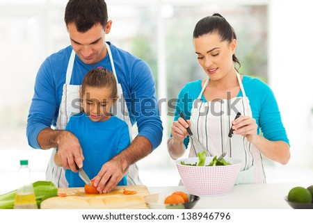 caring father teaching little daughter cutting vegetables while family cooking at home