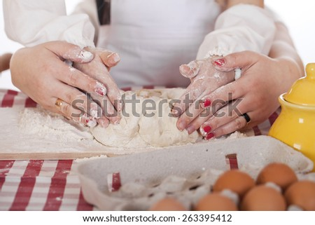 Caring Hands mother helping her daughter prepare dough - stock photo