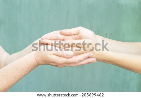 caring hands of a young girl and an old woman - stock photo